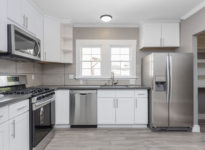 Kitchens in white new, with granite counter-tops, stove and stai