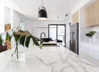 Kitchen marble bench close up with black hanging pendant and vas